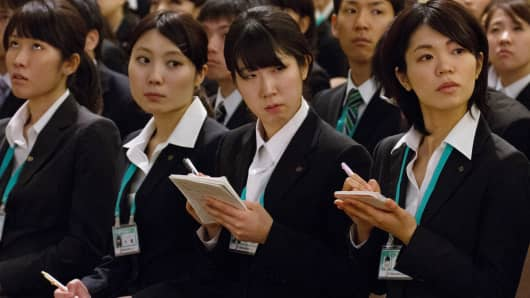 Seven & I Holdings Co. new employees take notes during an initiation ceremony in Tokyo.