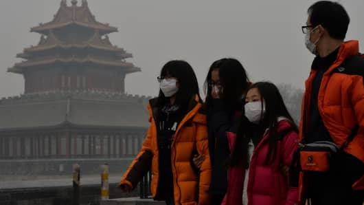 Chinese tourists wear face masks while walking past the Forbidden City in February 2014 as heavy air pollution shrouded Beijing.
