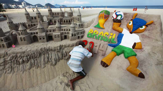 A man paints a 2014 World Cup design on a sand castle on Copacabana Beach in Rio de Janeiro, Brazil.