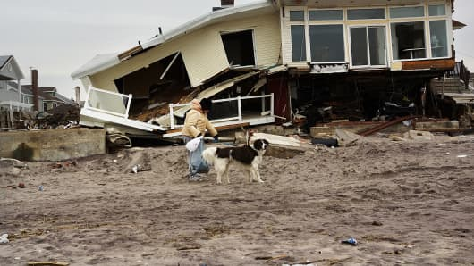 A woman walks with her dog by homes damaged by Hurricane Sandy along the beach in the Rockaways on January 15, 2013 in New York City.