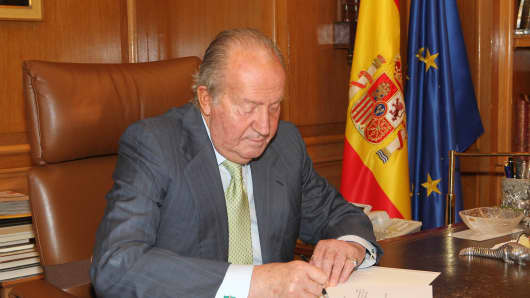 In this handout image provided by the Spanish Royal Palace, King Juan Carlos of Spain signs papers to confirm his abdication on June 02, 2014 in Madrid, Spain.