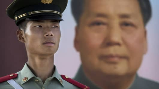 A Chinese officer stands guard under a portrait of the late Mao Zeding outside the Forbidden City at Tiananmen Square on June 2, 2014.