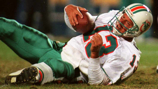 Miami Dolphins quarterback Dan Marino wears a weary scowl after he was sacked by New England Patriots defensive end Willie McGinest in fourth quarter action on Nov. 3, 1996.