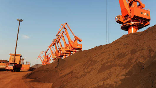 Large goods vehicles load iron ore at Qingdao port in Shandong, China.