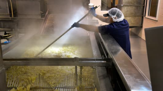 A worker makes sure that no chips stick to the kettle during cooking at Route 11 Potato Chips, March 6, 2014, in Mount Jackson, VA.
