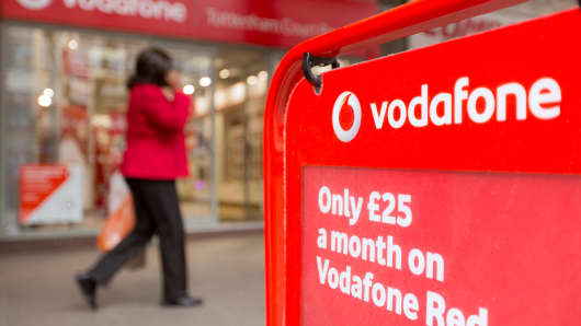A pedestrian walks past a Vodafone store in London.