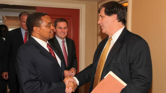 Bruce Wrobel (right) shakes hands with Tanzanian President Jakaya Kikwete (left) in September 2011 as members of the Blackstone Group and Sithe Global team look on.