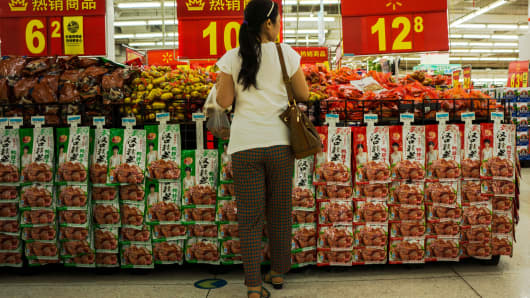 A female shopper stops at the best-selling goods shelf for all kinds of processed meat.
