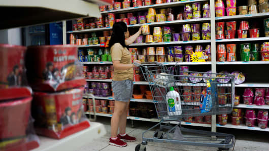 A shopper chooses instant noodles in a Wal-Mart store in China.