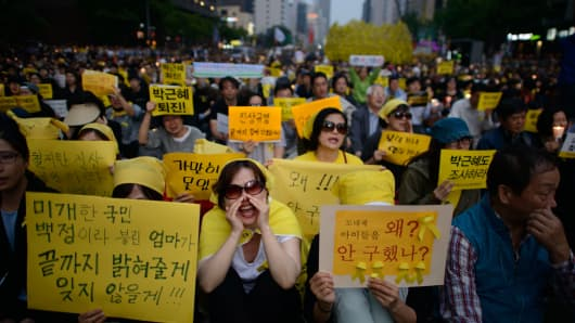 People shout slogans at a rally prior to a vigil for victims of the Sewol ferry and denouncing the government response to the disaster, in Seoul.