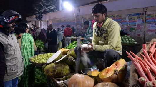An Indian man purchases vegetables from a roadside vendor.