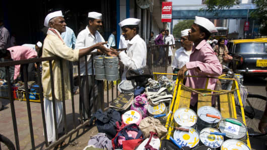 Delivery men sorting lunch boxes before delivery in front of Churchgate railway station in Mumbai, India.