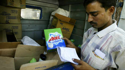 A deliveryman holds a packet of detergent powder as he checks the order list in New Delhi, India.