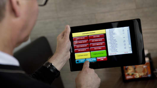 Mike Davidson, co-owner of Bolt Burgers, demonstrates a portable tablet computer for customers to order food and drinks at Bolt Burgers in Washington, DC.