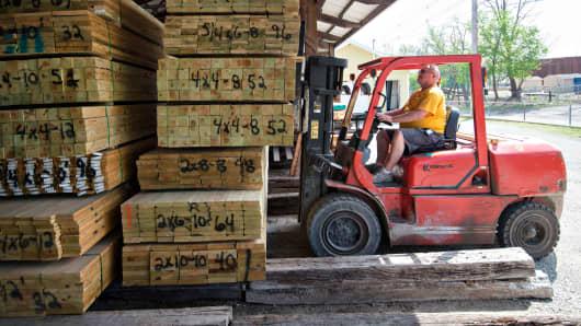 Employee organizes treated lumber at Maze Lumber in Peru, Illinois.