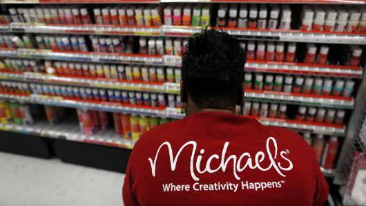 Employee Nikki Bush stocks acrylic paint at a Michaels Stores Inc. location in Cincinnati, Ohio.