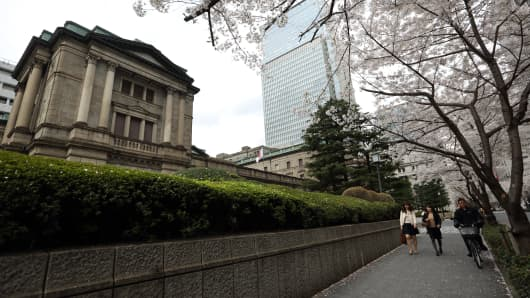 Pedestrians walk past the Bank of Japan headquarters in Tokyo, Japan.