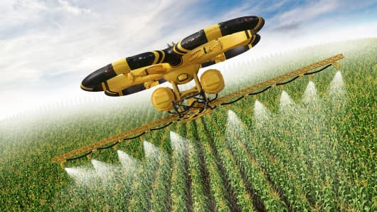 Flying utility drone spraying pesticide over a cornfield