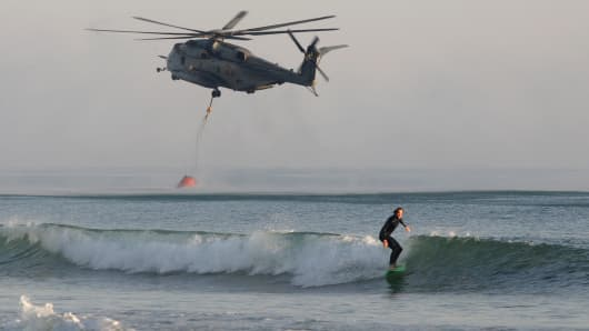 A surfer catches a wave as a CH 53 Super Stallion Marine helicopter scoops water from the Pacific to fight a fire at nearby Camp Pendleton, Calif., on May 16, 2014.