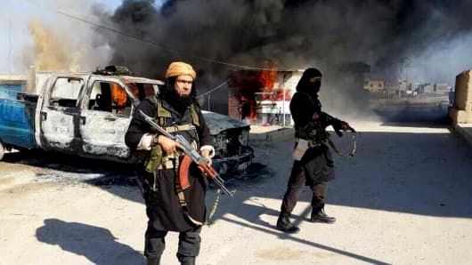 This undated file image posted on a militant website on Jan. 4, 2014, which is consistent with other AP reporting, shows Shakir Waheib, a senior member of the al-Qaida breakaway group Islamic State of Iraq and the Levant (ISIL), left, next to a burning police vehicle in Iraq's Anbar Province.