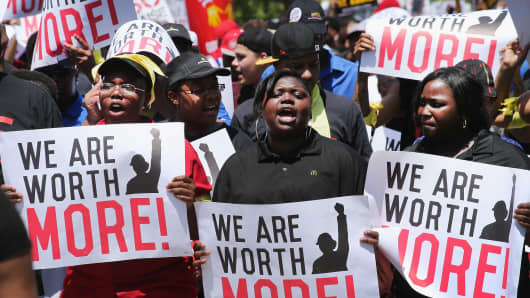 Fast-food workers and activists demonstrate outside the McDonald's corporate campus on May 21, 2014, in Oak Brook, Illinois. The demonstrators were calling on McDonald's to pay a minimum wage of $15 per hour and offer better working conditions for their employees.