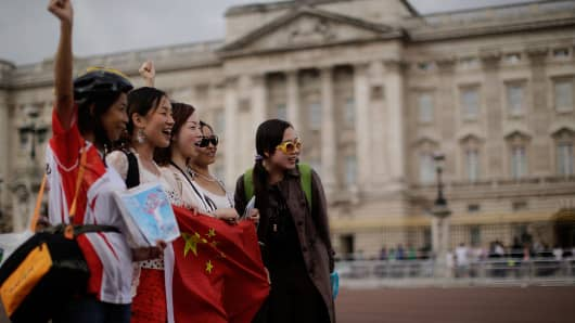 Chinese tourists have their pictures taken outside Buckingham Palace in London, England.