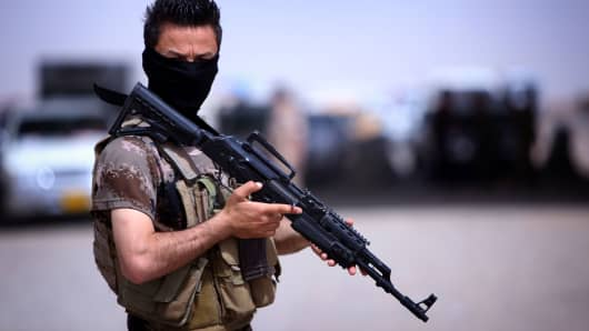 A masked Peshmerga fighter from Iraq's autonomous Kurdish region guards a temporary camp set up to shelter Iraqis fleeing violence in the northern Nineveh province, in Aski kalak, 40 kms west of the region's capital Arbil.