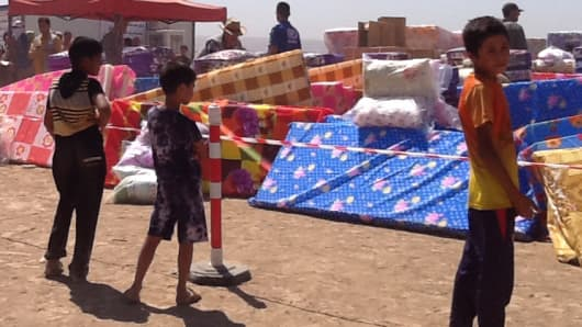 Young boys fleeing ISIS militants gaze on mattresses provided at a United Nations refugee camp east of Mosul, Iraq, on June 17, 2014.