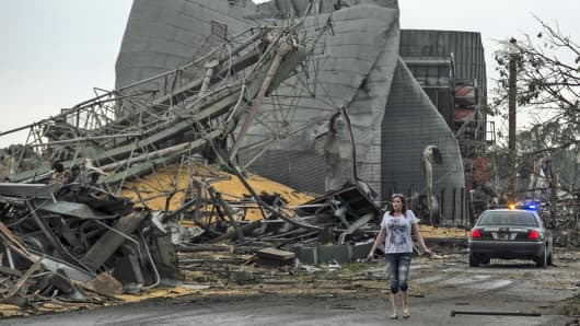 A woman walks down Black Hills Trail road in Pilger, Neb., Monday, June 16, 2014. At least one person is dead and at least 16 more are in critical condition after two massive tornadoes swept through northeast Nebraska on Monday.