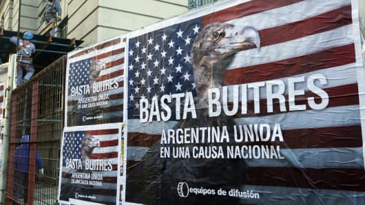 "Construction workers work near posters that read ""Enough vultures, Argentina united for a national cause"" in Buenos Aires June 18, 2014. Argentina is taking steps to place its restructured debt under local law so it can continue making payments despite a string of adverse U.S. court rulings."