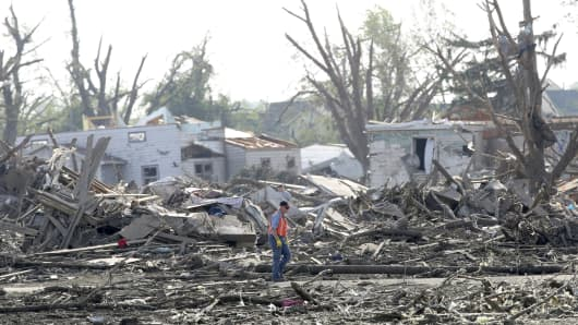 A man walks through debris in  Pilger, Nebraska, after a tornado swept across the farming area in northeast Nebraska on June 16, 2014.