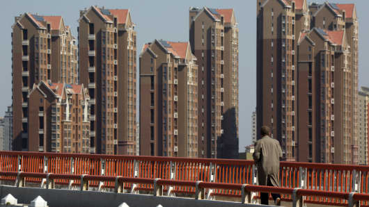 A pedestrian walks on a bridge in front of residential buildings at the Sino-Singapore Tianjin Eco-city in Tianjin, China.