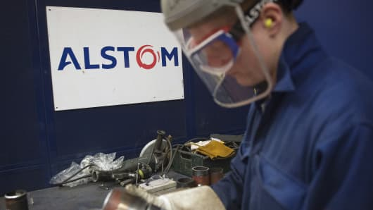 An apprentice inspects a section of cut metal at Alstom SA's welding training facility in Stafford, U.K.
