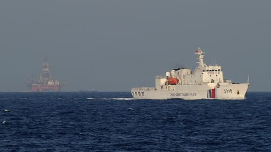 A Chinese coast guard vessel (R) sailing near China's oil drilling rig in disputed waters in the South China Sea.