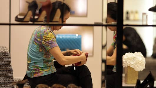 A customer sits behind the window display of a Chanel store at Lotte Shopping's department store in Seoul, South Korea.