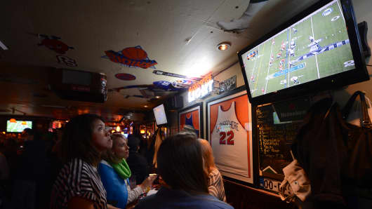 Football fans watch the NFL Super Bowl XLVIII game between the Denver Broncos and the Seattle Seahawks on at a sports bar in New Jersey on February 2, 2014.