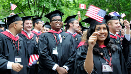 Graduates from the Harvard Business School MBA program wave flags at commencement in Cambridge, Mass.