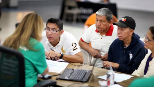 People sit with an insurance agent as they purchase health insurance under the Affordable Care Act in Miami.
