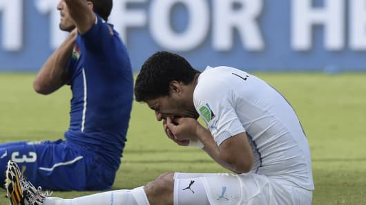 Uruguay forward Luis Suarez (R) puts his hand to his mouth after clashing with Italy's defender Giorgio Chiellini.