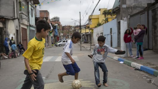 Children play football in the street in the poor neighbourhood of Itaquera, adjacent to the 'Arena de Sao Paulo' stadium, on June 21, 2014 in Sao Paulo, Brazil.