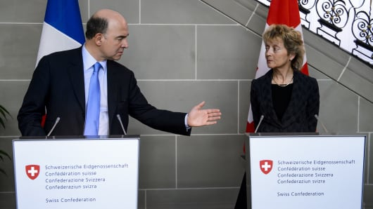 French Economy, Finance and Foreign Trade Minister Pierre Moscovici (L) gestures next to Swiss Finance Minister Eveline Widmer-Schlumpf after discussing everal bilateral issues related to the tax system, cooperation in tax compliance, and cross-border workers on March 6, 2014.