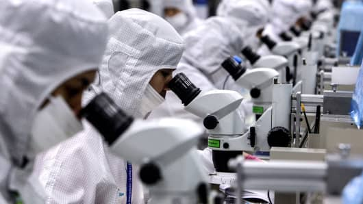 Employees inspect semiconductor chips on the production line at the Hana Microelectronics plant at the Hi-Tech Industrial Estate in Thailand.
