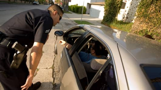 A Los Angeles police officer pulls over a car for an ownership check in the Wilshire neighborhood after a report went out of a similar model and color being stolen in Los Angeles, California.
