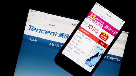 The JD.com website is displayed on an Apple Inc. iPhone 5s on top of an Apple iPad displaying the Tencent Holdings Ltd. website.