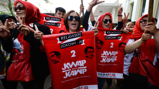 A group of supporters holding red banners of Joko Widodo, governor of Jakarta and presidential candidate, wait to greet Widodo as he arrives for an election campaign in West Java province, Indonesia.