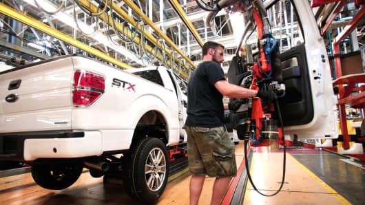 A Ford worker performs a door install on a new 2014 Ford F-150 truck on the assembly line at the Ford Dearborn Truck Plant, June 13, 2014 in Dearborn, Mich.