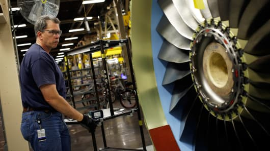 A production assembly mechanic prepares to install a bracket on a CFM56-7 jet engine at General Electric Co.'s GE Aviation factory in Cincinnati, Ohio, June 25, 2014.