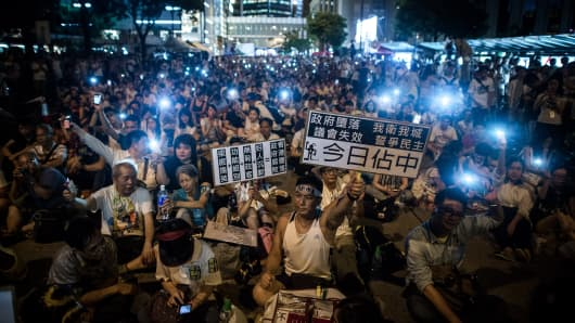 Demonstrators sit in a street of the central district after a pro-democracy rally seeking greater democracy in Hong Kong on July 1, 2014.