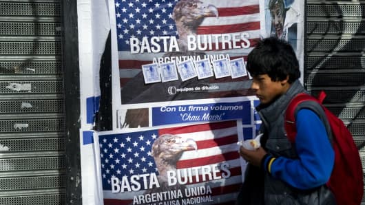 A young man passes by posters on a wall against the 'vulture funds' in Buenos Aires on June 18, 2014.
