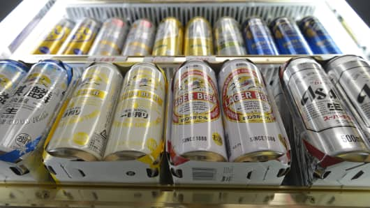 Cans of various brands of Kirin Brewery beer and Asahi Breweries' Asahi Super Dry beer are displayed for sale in Kawasaki, Japan.